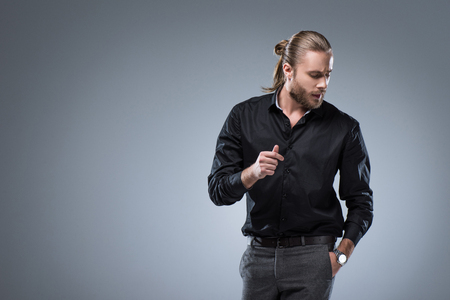 Long haired man in black shirt  looking down with hand in pocket, isolated on gray Stock Photo