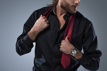 Cropped image of bearded man in black shirt with red tie around his neck,  isolated on gray