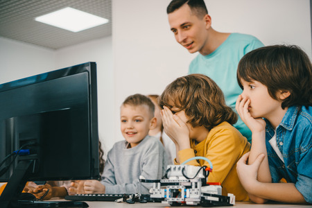 teacher programming robot with his teen students Stock Photo