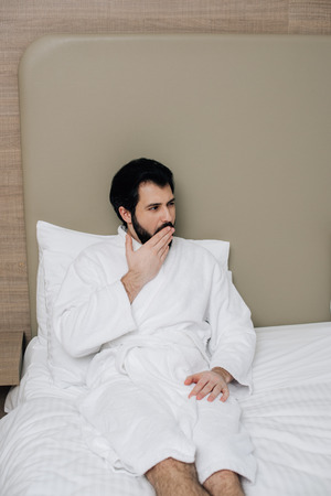 handsome man in bathrobe sitting in bed at hotel suite and yawning