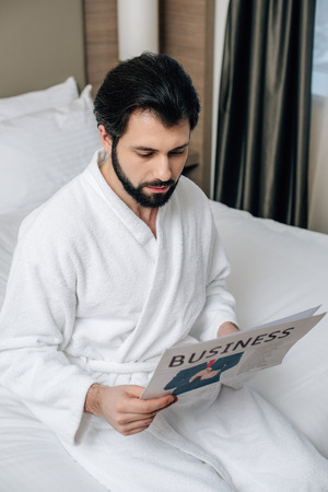 serious businessman in bathrobe reading newspaper at hotel suite