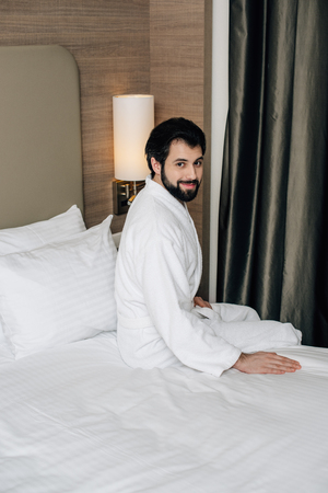 happy man in bathrobe sitting on bed at hotel suite