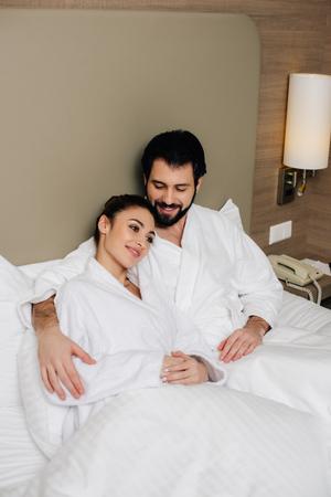 happy couple in bathrobes embracing in bed of hotel suite Standard-Bild - 114616301