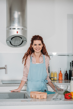 smiling woman standing in kitchen and looking at camera Archivio Fotografico - 114549212