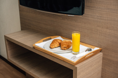 croissants and orange juice on wooden tray