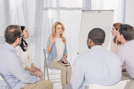 middle aged woman holding hand on Holy Bible while sitting with multiethnic people on chairs at group therapy
