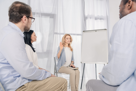 middle aged woman with closed eyes holding hand on Holy Bible during anonymous group therapy