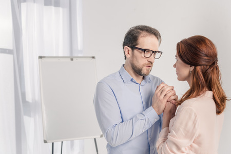 middle aged man and woman holding hands and looking at each other Stock Photo - 114549412