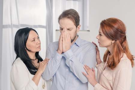 multiethnic women supporting depressed middle aged man during group therapy
