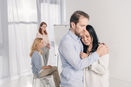 mature man hugging depressed asian woman during group therapy