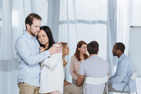 upset mature couple hugging while people sitting on chairs behind during group therapy Stock Photo