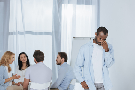 middle aged african american praying while people sitting behind during group therapy Stock Photo - 114549487