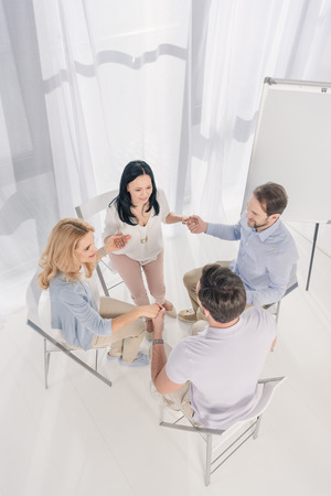 overhead view of middle aged people sitting and holding hands during group therapy