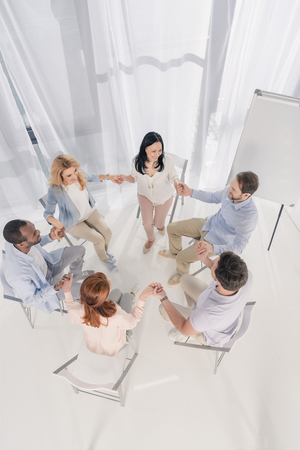 overhead view of middle aged multiethnic people sitting on chairs and holding hands at group therapy Stock Photo