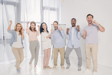 cheerful multiethnic middle aged people triumphing and smiling at camera Stock Photo - 114549544