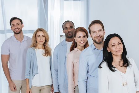 multiethnic mid adult people standing together and looking at camera