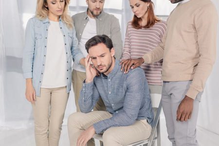 cropped shot of middle aged multiethnic people supporting upset man during group therapy