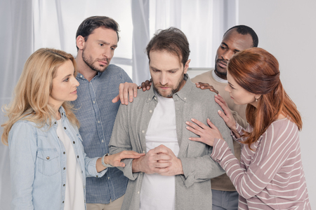 middle aged multiethnic people supporting sad man during group therapy