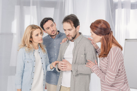 people supporting upset middle aged man during group therapy Stock Photo - 114549555