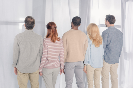 back view of multiethnic people standing together during group therapy