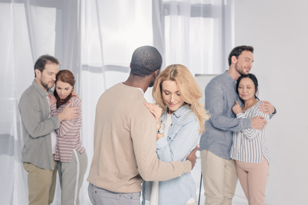 three multiethnic couples hugging during psychotherapy Stock Photo - 114549563