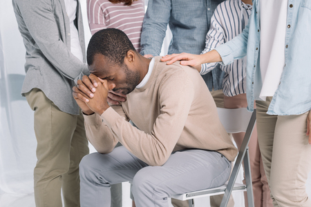 cropped shot of people supporting depressed middle aged african american man during group therapy Foto de archivo