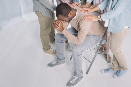 high angle view of people supporting depressed african american man during group therapy