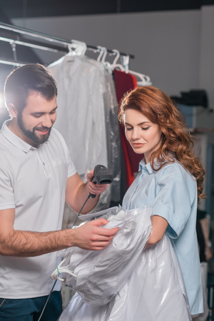 dry cleaning workers scanning barcode on bag with shirt