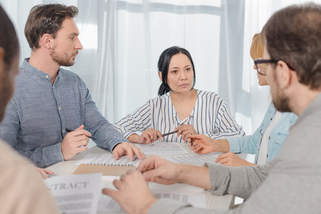 middle aged multiethnic people signing contract at anonymous group therapy