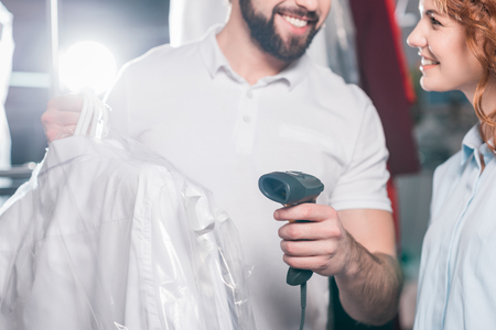 cropped shot of dry cleaning workers scanning bag with clothes