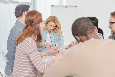 multiethnic people gathered together and taking notes during group therapy Stock Photo - 114549646