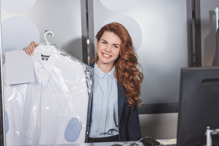 happy dry cleaning manageress holding shirt on hanger packed in plastic bag