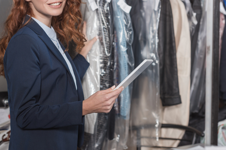 cropped shot of dry cleaning manageress using tablet