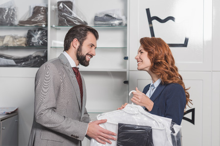 dry cleaning manageress giving bag with clothes to happy man