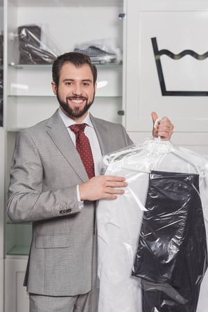 businessman holding plastic bag of clean clothing at dry cleaning Banco de Imagens