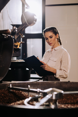 portrait of focused coffee roaster with notepad checking work