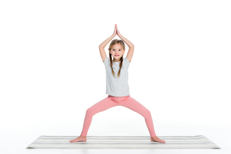 kid practicing yoga on yoga mat isolated on white 免版税图像
