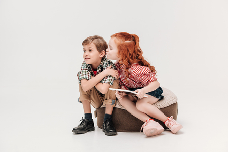 adorable little girl holding digital tablet and able to kiss little boy isolated on grey Stock Photo