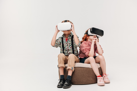 cute little children sitting and using virtual reality headsets isolated on grey