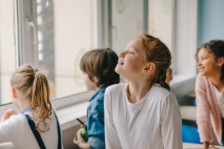 adorable schoolchildren looking at window together at classroom