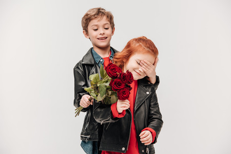 happy boy presenting roses bouquet to his little girlfriend isolated on grey Stock Photo