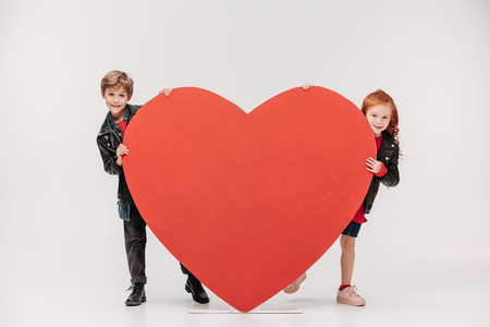 funny little kids couple hiding behind large red heart isolated on grey 写真素材 - 114550950