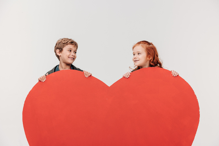smiling little kids couple behind large red heart isolated on grey 写真素材 - 114550952