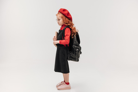 side view of adorable little schoolgirl in red beret with book and backpack isolated on grey Imagens