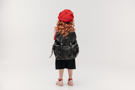 read view of little schoolgirl with large backpack isolated on grey Imagens