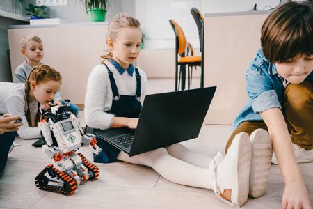 Niños programando robot mientras están sentados en el piso en la clase de educación de Stem