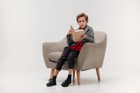 focused little schoolboy reading book in armchair