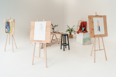 easels with paintings in empty art studio Stock Photo
