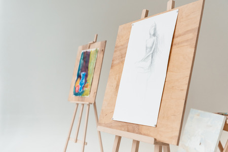 easels with artistic paintings in empty art studio on grey
