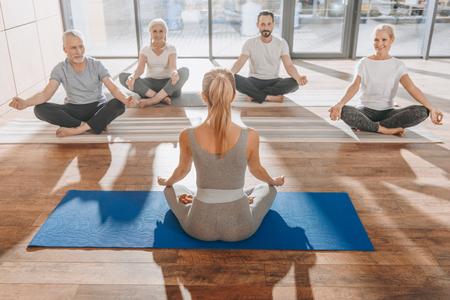 Gruppe von Frauen, die in Lotus-Yoga-Pose mit Mudra des Wissens meditieren Standard-Bild